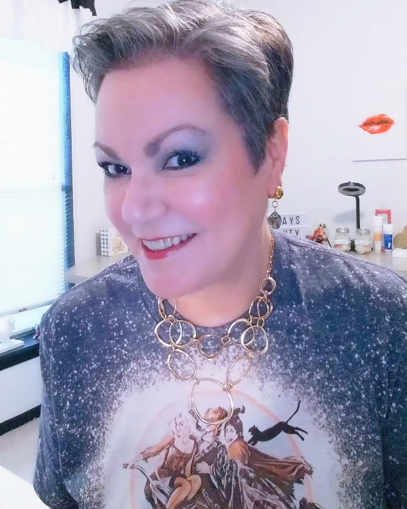 Wearing fmg Glimmer Eyeshadow Palettes Vixen and Goddess from Avon.  Pixie Style Natural Gray Hair Style. Hocus Pocus T-shirt and Avon Jewelry.